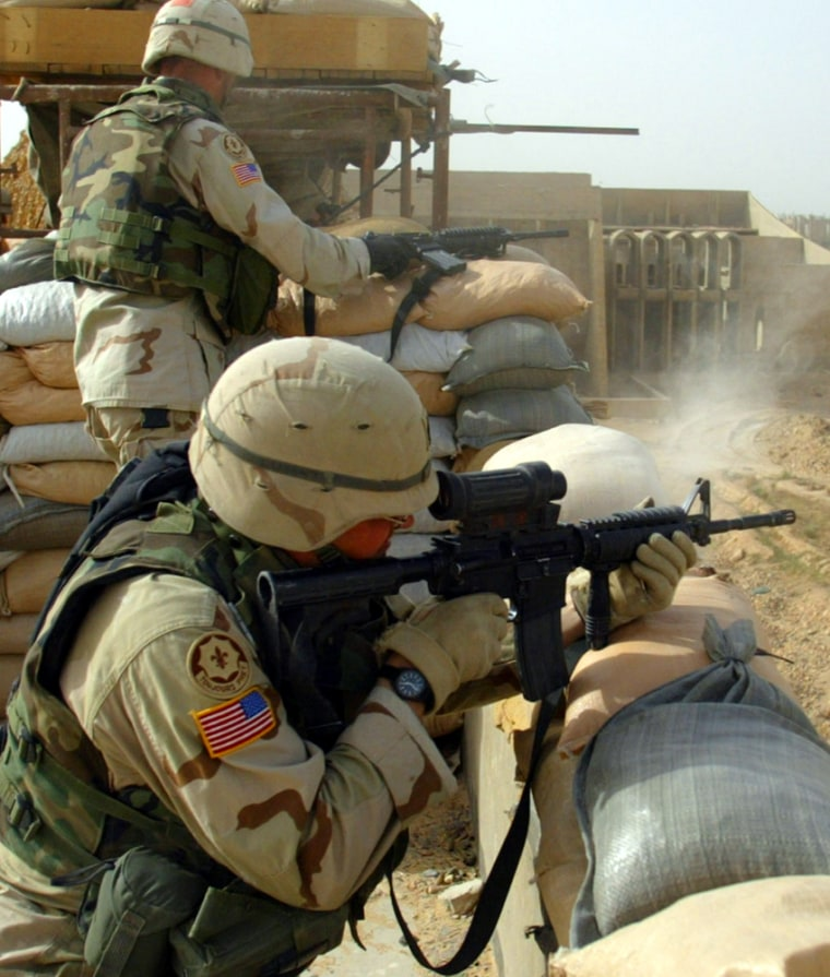 A U.S. soldier from the 2nd Armed Cavalry Regiment shoots an M-4 assault rifle at insurgents in Najaf on Monday.