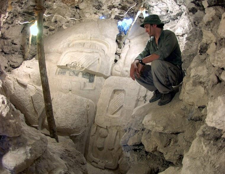 Archaeologist Francisco Estrada-Belli is dwarfed by thehuge stucco face of a Maya deity, found at Cival,Guatemala.