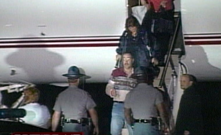 Former hostage Thomas Hamill, in glasses,center, arrives at a small airport near Macon, Miss., early Saturday.