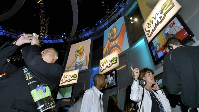 """Visitors browse""""The Sims 2"""" at the Electronic Entertainment Exposition in Los Angeles. In the sequel, Sims can now feel love -- and lust."""