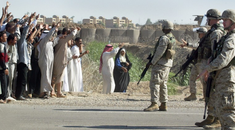 Marines stop Iraqis from approaching a bus with 40 released detainees leaving the Abu Ghraib prison on Friday.
