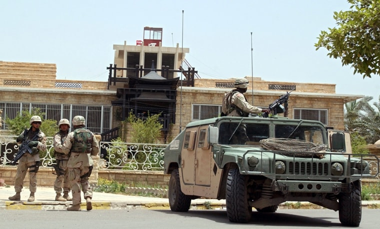 U.S Army soldiers stand guard Thursday outside the residence of Iraqi politician Ahmad Chalabi in Baghdad.