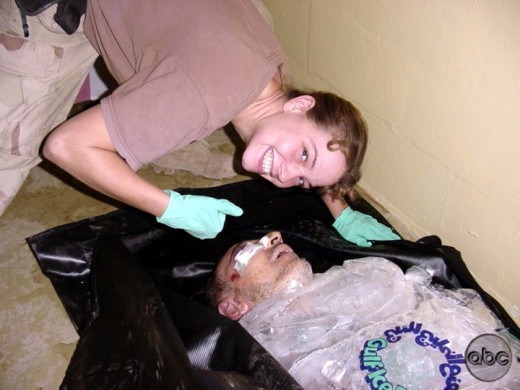 In this undated photo, obtained by ABC News and allegedly taken by Sgt. Charles Frederick in Abu Ghraib prison in Baghdad, Iraq, Army Spc. Sabrina Harman of the 372nd Military Police Company poses with the body of a dead Iraqi man packed in ice.