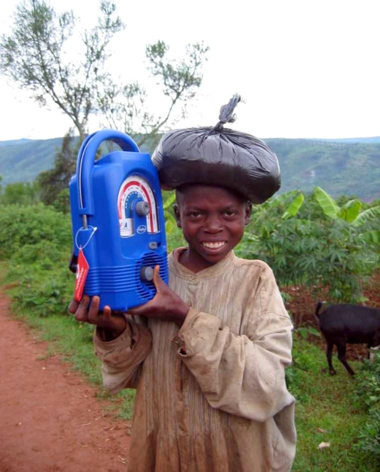 A young boy listens to a Lifeline radio in Mugumbazi, Rwanda.