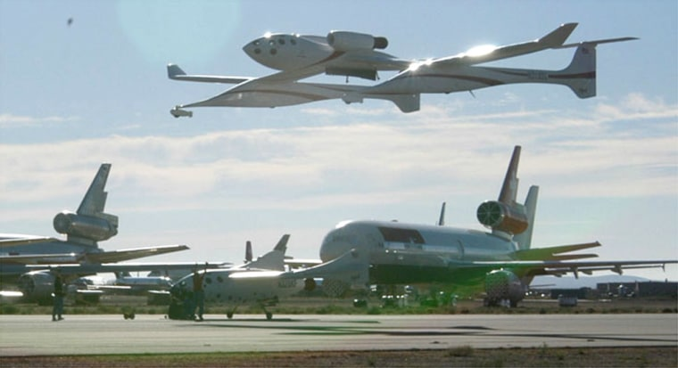 Scaled Composites'White Knight carrier aircraft makes a low pass over the SpaceShipOne rocket plane, surrounded by other planes parked at the Mojave Airport in California.