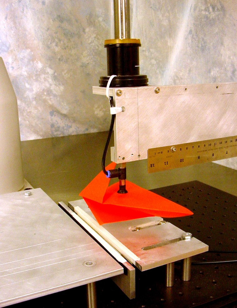Balkcom's robot uses a tiny suction cup attached to a mechanical arm to pick the paper up, rotate it and place it on the worktable.