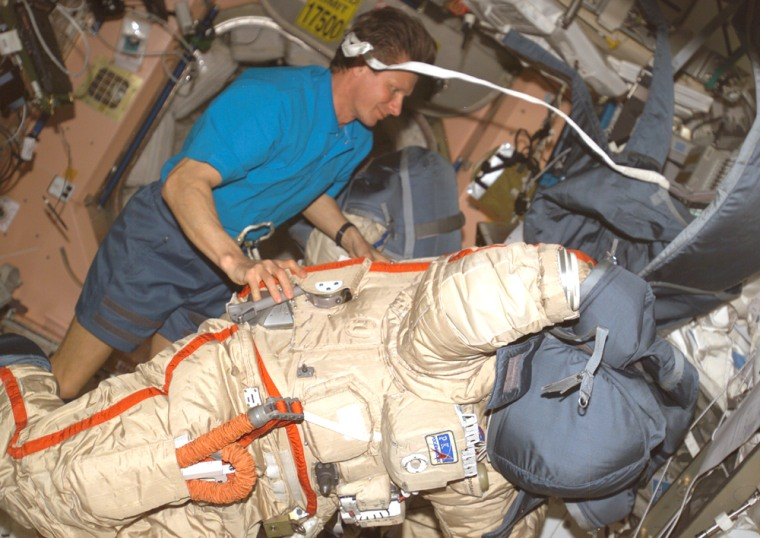 Russian cosmonaut Gennady Padalka, the international space station's commander, checks out his Orlan spacesuit. Such suits will have to be used during a spacewalk next month because of problems with two of the three U.S.-made spacesuits designed for extravehicular activity.