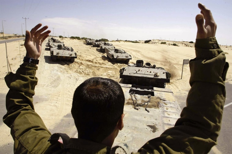 An Israeli soldier gives instructions toarmored vehicle driversMonday as theypassthe Rafiah Yam settlementin the southrn Gaza Strip after pulling out of the nearby Palestinian town of Rafah.