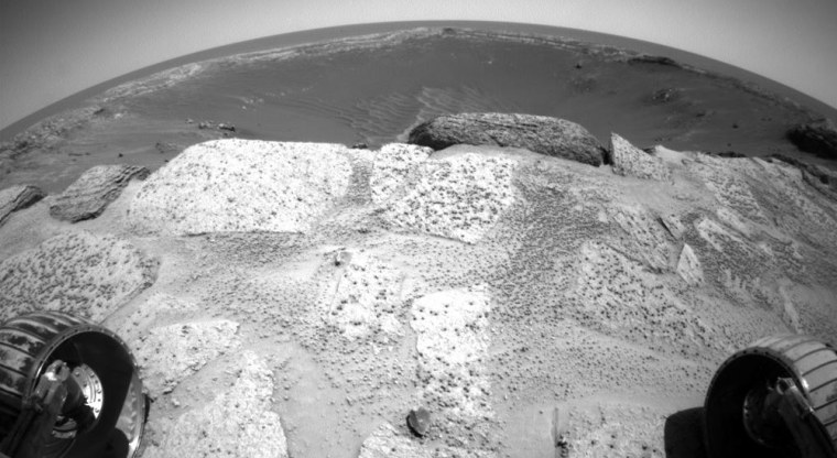 """This wide-angle view from a hazard avoidance camera on NASA's Opportunity rover shows slabs of rock strewn with """"Martian blueberries"""" in the foreground,with the stadium-sized Endurance Crater stretching out beyond the brink."""