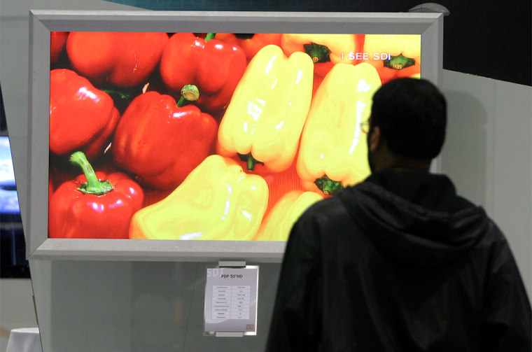 A vendor watches a Samsung ultra fine PDP 63-inch HD screen at the Society for Information Display expo in Seattle.