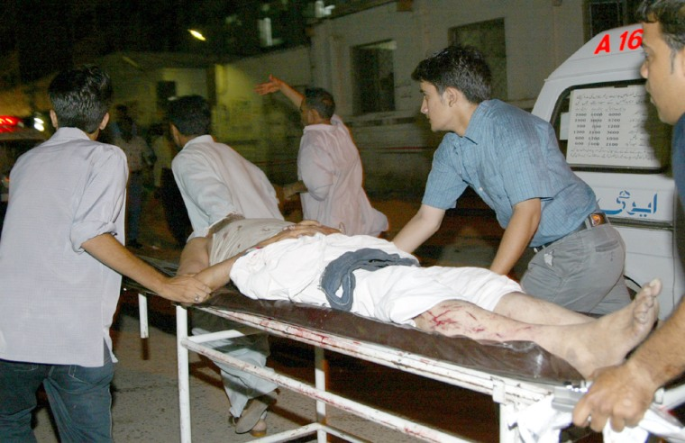 VOLUNTEERS MOVE AN INJURED WORSHIPPER AFTER A BOMB EXPLOSION IN KARACHI