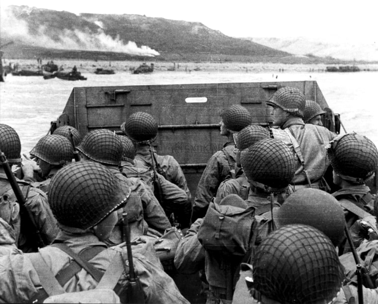 Troops in a landing craft huddle behind the protective front as it nearsOmaha Beach on D-Day. The soldier directly to the left of the tall soldier at the front of the craft is
