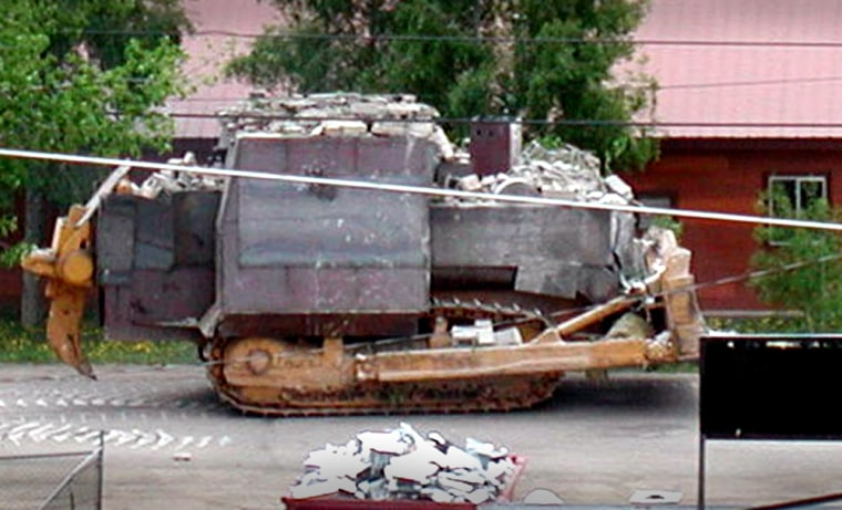 A man later identified asMarvin Heemeyer drives his fortified bulldozer down Jasper Street in Granby, Colo., on Friday. Heemeyer was later found dead.
