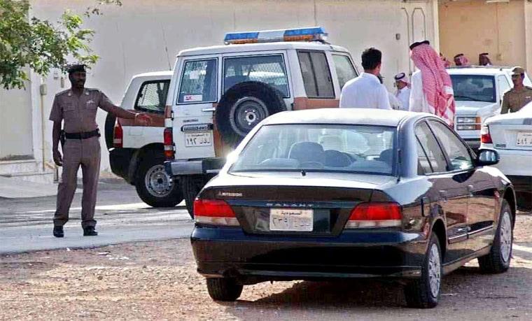 Saudi police and neighbors of the Riyadh neighborhood stand outside the buildingwhere an American was killed Tuesday.