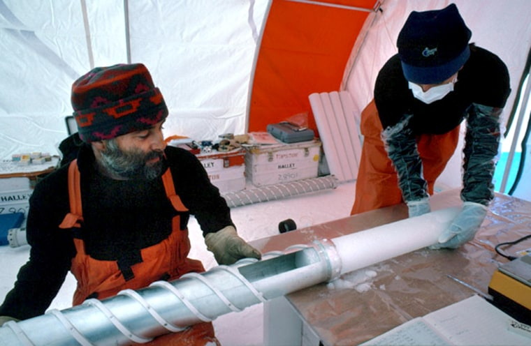 Researchers remove ice core from a drill at their remote Antarctic station.