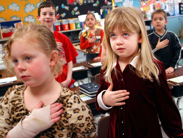 Jessica Dierkes,left, and Amanda Gehring — first grade students at Longstreth Elementary School — pledge allegiance to the flag March 24 in Warminster, Pa.