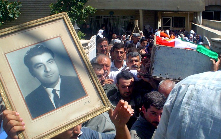Mourners carry a portrait of, and the Kurdish flag-draped coffin containing, Ghazi Talabani, the top security official for the state-run Northern Oil company, during his funeral in Kirkuk on Wednesday.