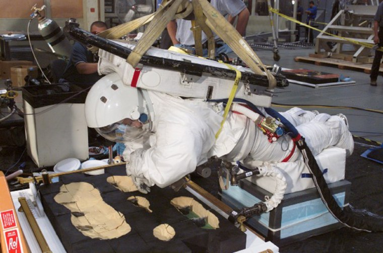 EVA Operations Engineer Dana Weigel, dressed in a spacesuit,participates in an evaluation of shuttle tile repair techniques in the Space Environment Simulation Laboratory at NASA's Johnson Space Center. The board is a simulated section of tile, with dense yellow foam as a substitute for the tiles.
