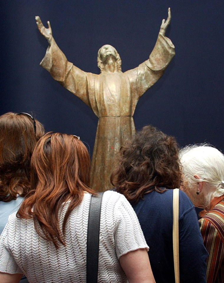 People flock to see a bronze statue of Christ in Genoa, Italy, on Friday. A woman claimed that she saw the face of the popular Italian saint Padre Pio on the figure's chest, sparking the controversy.