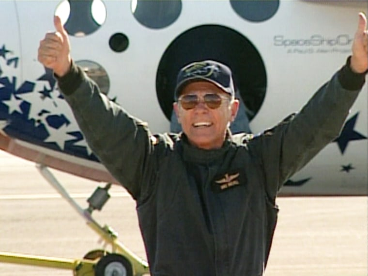 SpaceShipOne test pilot Mike Melvill, America's newest astronaut,flashes a broad grin and thumbs-up signs after emerging from his rocket plane.