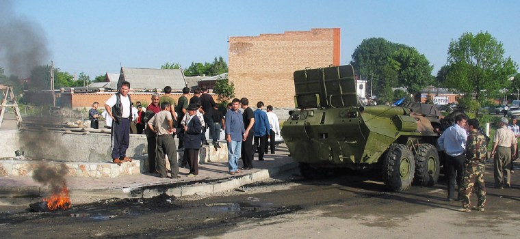 Civilians look at a damaged armored pers
