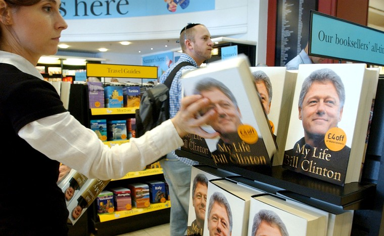 "An employee at a central London bookstore replenishes a display holding former President Bill Clinton's new autobiography, ""My Life,"""" on Tuesday."