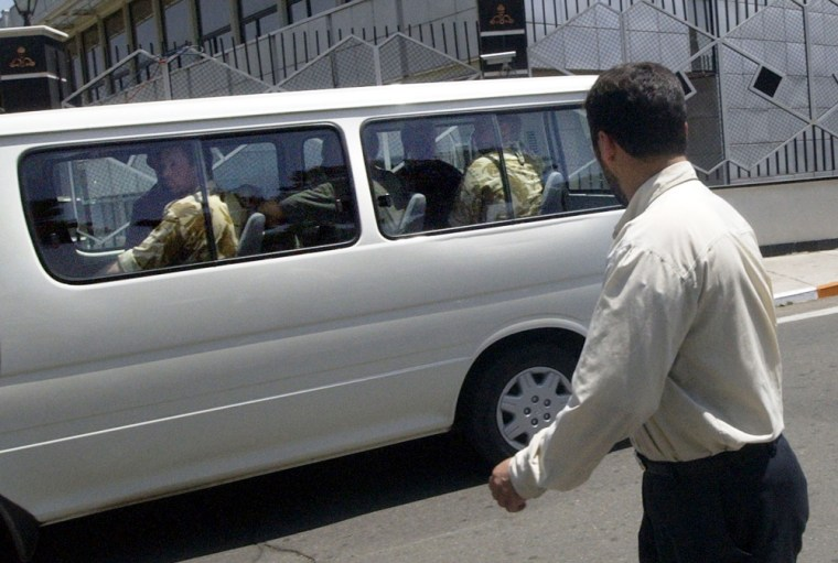 Eight British servicemen sitting inside a vehicle are watched by an Iranian securityguard as they arrive at Mehrabad airport in Tehran, Iran on Thursday.