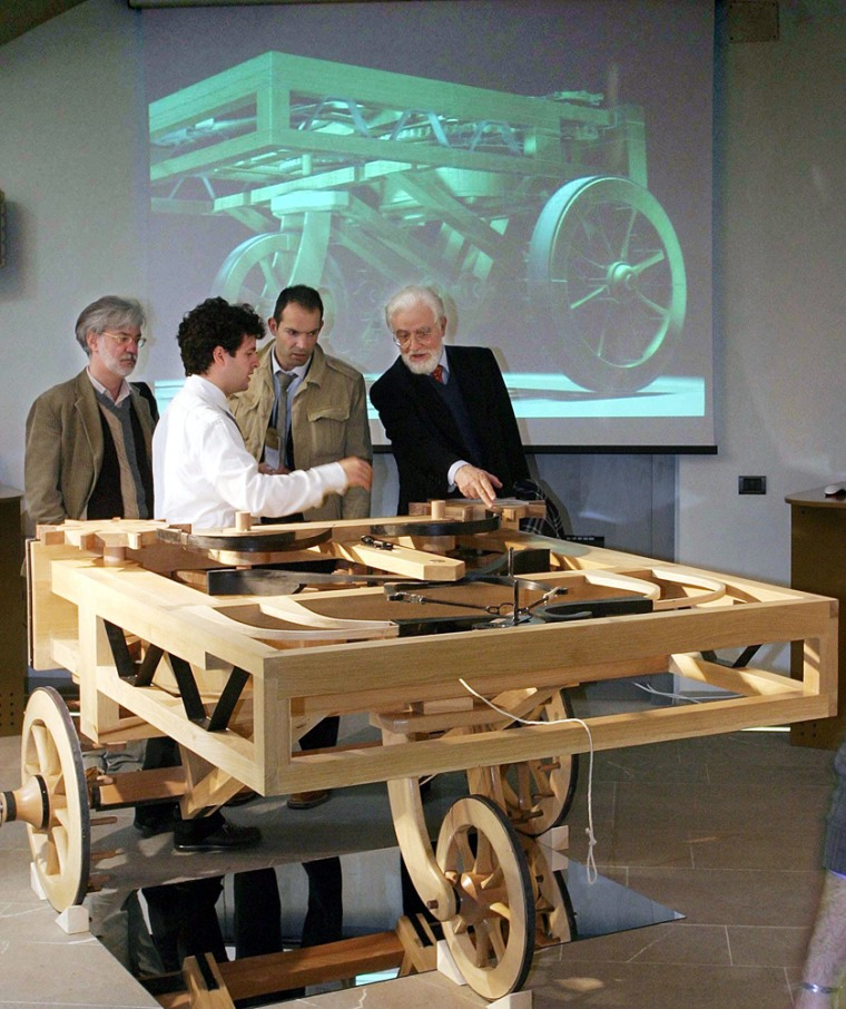 Journalists look at a wooden model of a car designed by Renaissance genius Leonardo da Vinci on display at an exhibition in Florence's Science Museum, Italy. Florentine engineers have built three new machines, based on Leonardo's plans, thatcouldn't have functioned using the materials available during his life.