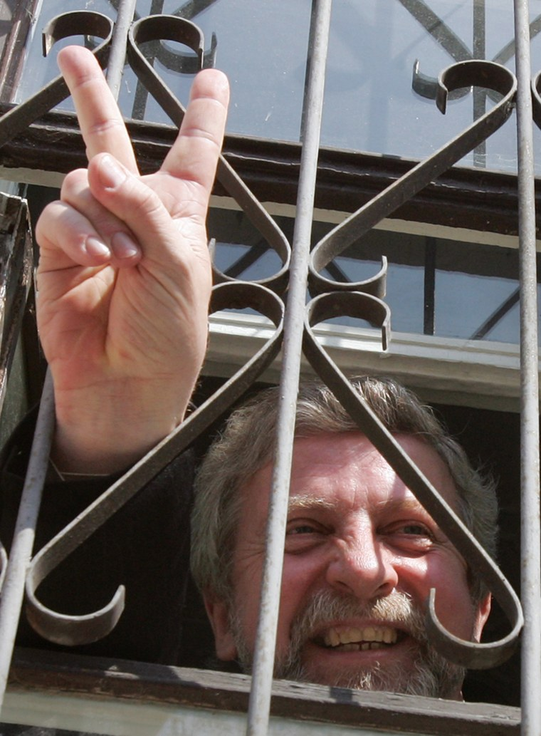 Opposition leader Milinkevich flashes victory sign from court room in Minsk