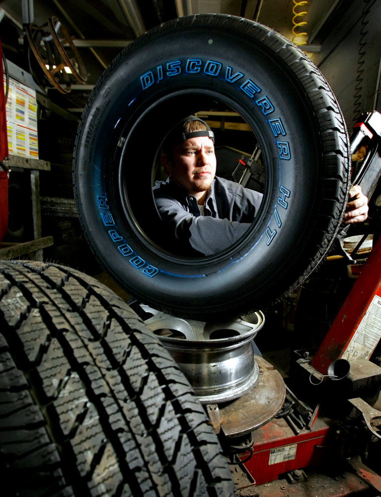William Hall inspects a Cooper Discoverer tire at the North Ridgeville Tire Company in North Ridgeville, Ohio.Simple tire maintenance steps canhelp motorists drive more safely and savegas.