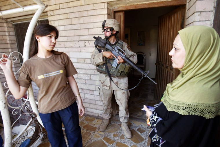 Iraqi women wait while U.S.soldiers search a home during a weapons raid in the Yarmouk section of Baghdad on Sunday.