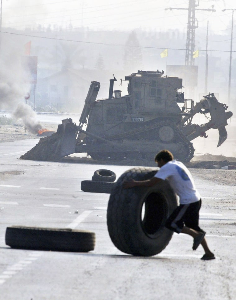 A Palestinian rolls a tire to erect a burning barricade to impede the advance of Israeli bulldozers and tanks Tuesday in the Gaza town of Beit Hanoun.