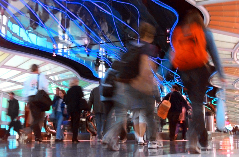 TRAVELERS HUSTLE THROUGH UNITED AIRLINES TERMINAL AT O'HARE AIRPORT