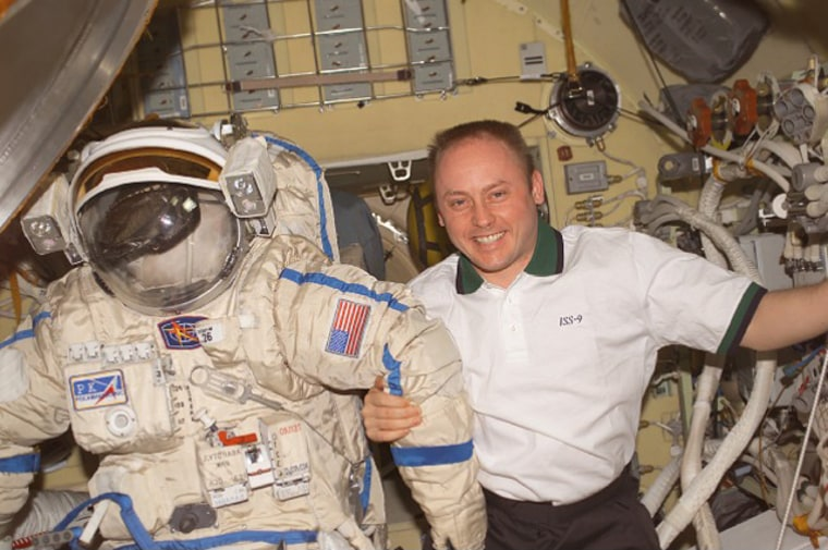 U.S. astronaut Mike Fincke stands next to his spacesuit aboard the international space station.
