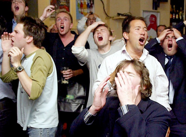 English fans react as they watch the Euro 2004 quarterfinal soccer match between Portugal and England on the big screen at the Elusive Camel pub in Victoria, London last week.