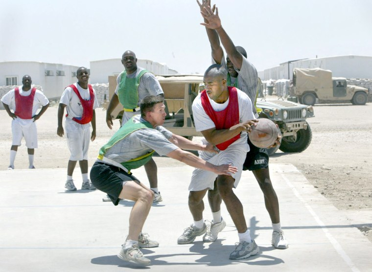 Teams from the U.S. Air Force 732 Expeditionary Civil Engineering Squadron, in red and white, and the U.S. Army 28th Signal Battalion, in green, play 3-on-3 basketball at Camp Victory near Baghdad,on Sunday.