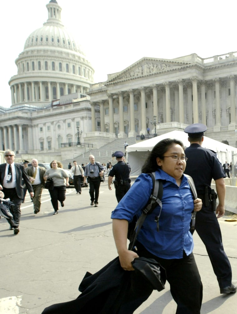 PEOPLE RUN FROM THE CAPITOL BUILDING DURING AN EVACUATION IN WASHINGTON