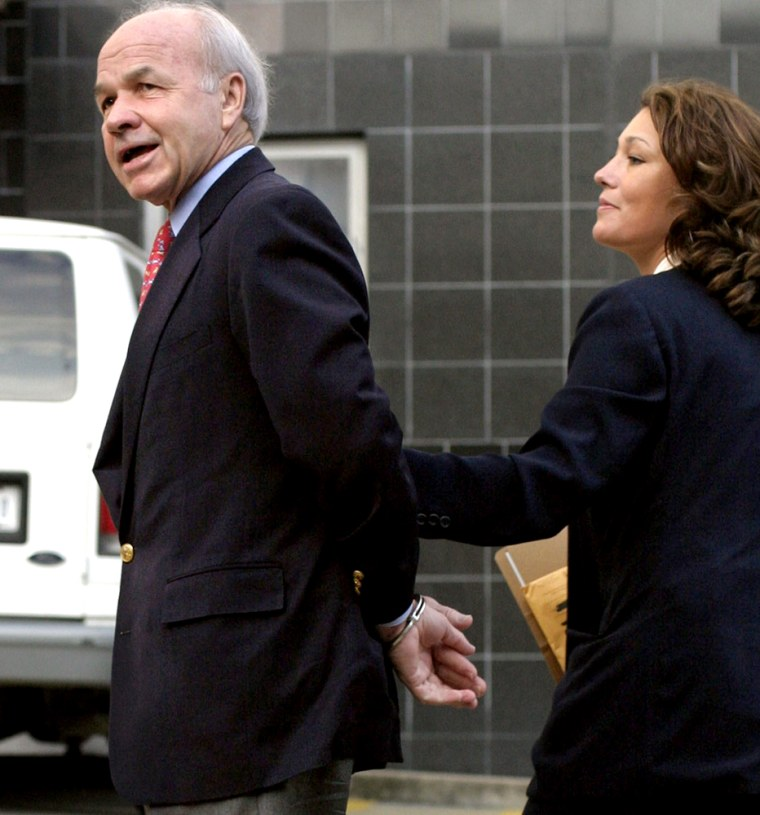 Former Enron CEO Kenneth Lay, left, is led into Federal Court by law enforcment officers in Houston Thursday.