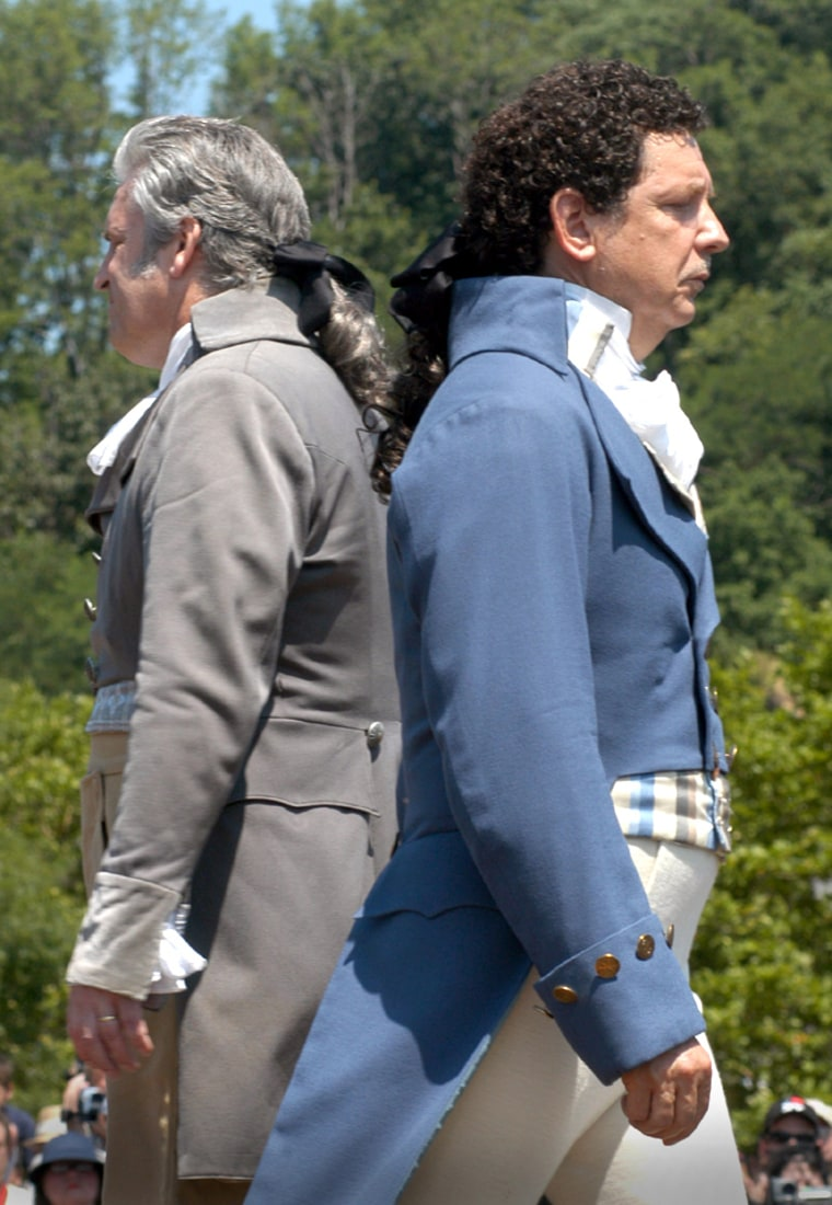 Douglas Hamilton, right, a fifth-great-grandson of Alexander Hamilton, passesAntonio Burr, a descendent of Aaron Burr's cousin, while they assume position for the 200th anniversary historic reenactment of the Hamilton-Burr duel in Weehawken, N.J.
