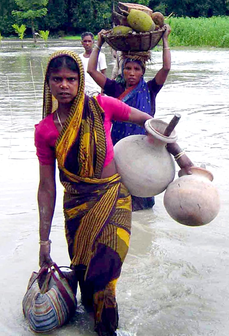 VILLAGERS WADE THROUGH A FLOODED AREA OF BALARAMPUR