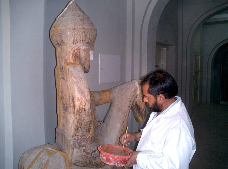 Shairazuddin Saifi, Director of the Kabul Museum restoration department, works on anantique horse.