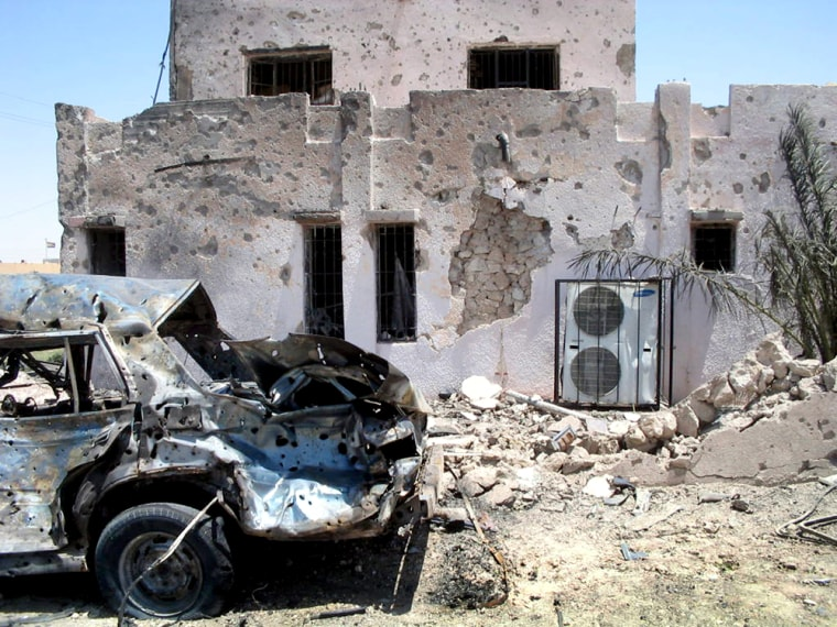 A vehicle used in a car bombing sits upended next to a police station Thursday in Haditha, Iraq.The blast killed 10 people in a second day of violence.