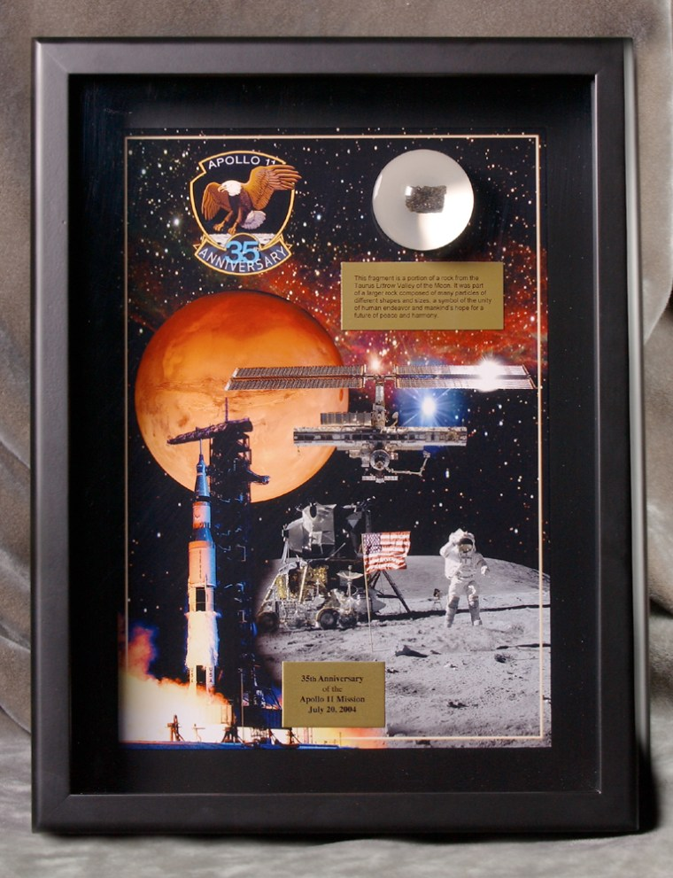 The plaques show a collage of images from the past and present space program, with the moon rock chip in a plexiglass disk in the upper right corner.