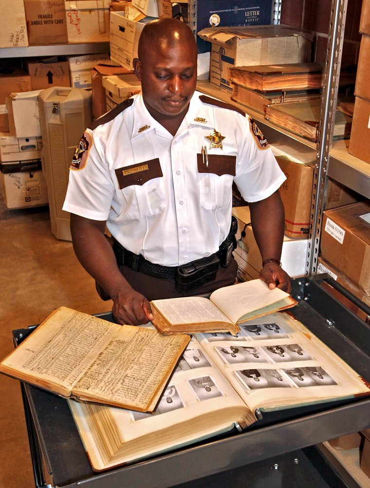 Montgomery County Chief Deputy Derrick Cunningham looks through pages of log books and booking photos Friday in the basement of the Montgomery, Ala., sheriff's office.