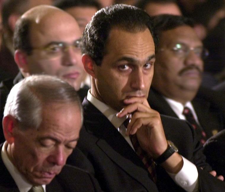 Egyptian President Hosni Mubarak's eldest son, Gamal, center, attends a midnight mass on Coptic Christmas Day last year.