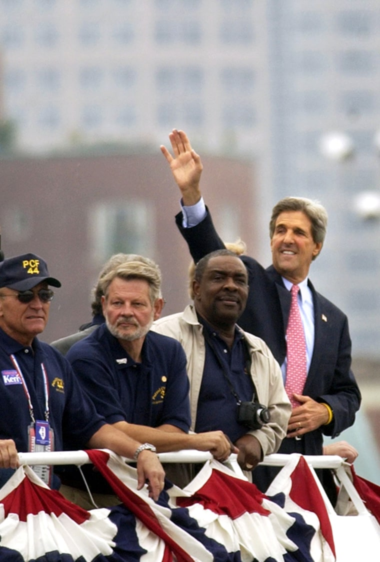 Democratic presidential candidateJohn Kerry waves to well-wishers from the deck of awater taxi Wednesday as he crossesBoston harbor. Accompanying him were several of his Vietnam-era swiftboat crewmates.