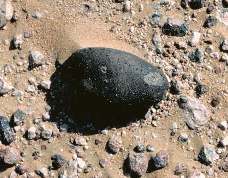 The dark meteorite Sayh al Uhaymir 169, is shownin the spot where it was found in the Omani desert.