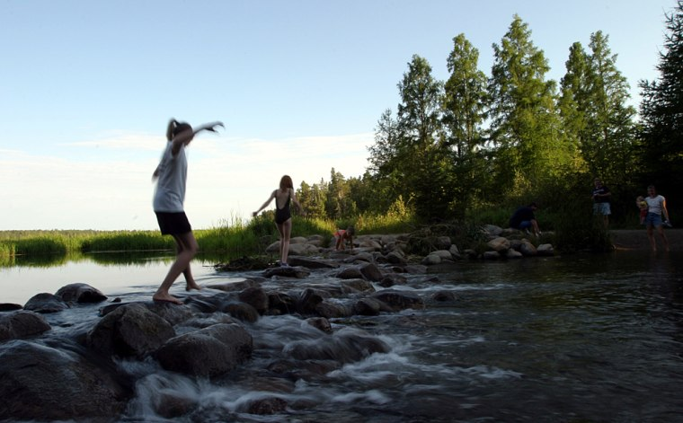 Children walk across the rocks at the outlet of Lake Itasca where the lake water becomes the Mississippi River in northern Minnesota.