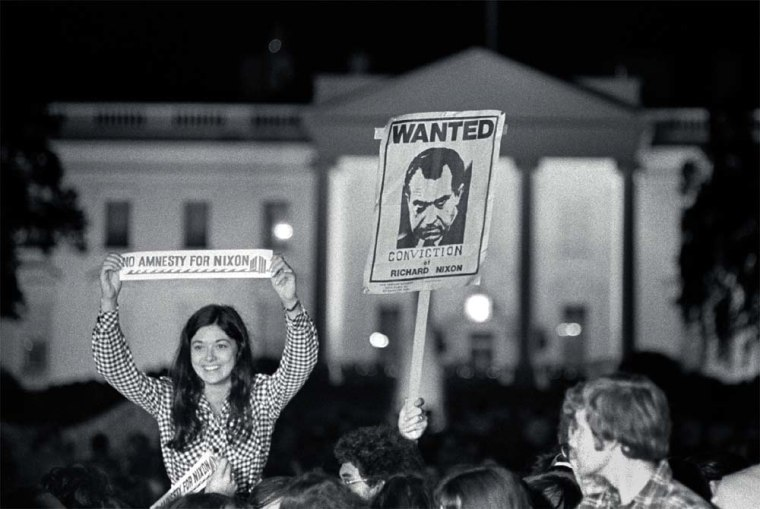 """A crowd celebrating Nixon's resignationhold """"Wanted Conviction of Richard Nixon"""" and """"No Amnesty for Nixon"""" signs outside the gates of the White House."""