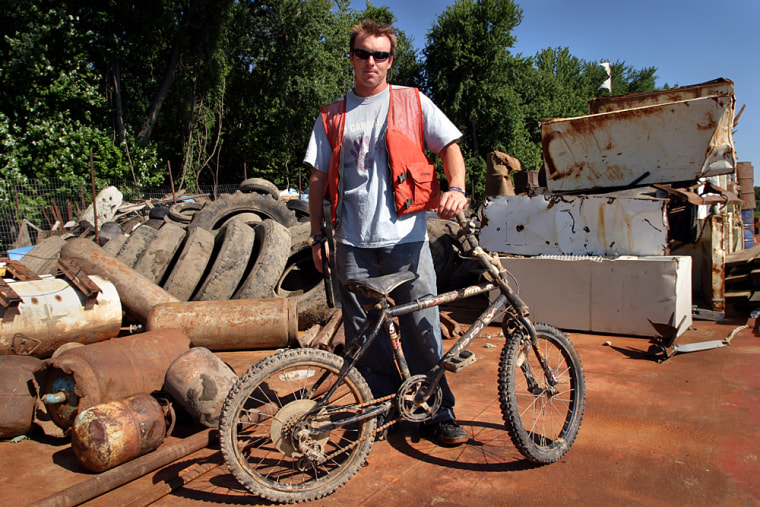 Founder of Living Land and Waters Chad Pregracke stands among piles of garbage he and his team removed from the Misssissippi River.  By his calculations, the cleanups have now removed more than 2 million pounds of trash from the river.